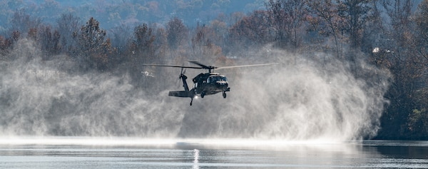 A West Virginia Army National Guard UH-60M Blackhawk helicopter flys low, close to river surface, creating a misty cloud around the helicopter.