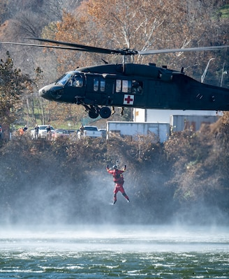 A side view of a West Virginia National Guard Blackhawk Helicopter airlifting a participant wearing an orange wet suit out of the Kanawha River.