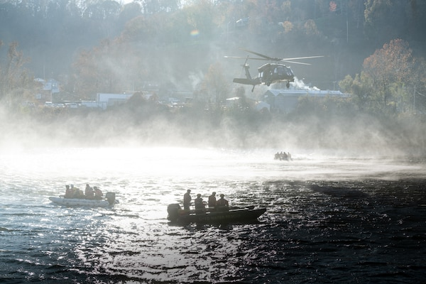 Three swift water boats below a Blackhawk helicopter, in a silhouette with the sun behind and rotor wash creating a misty fog across the river.
