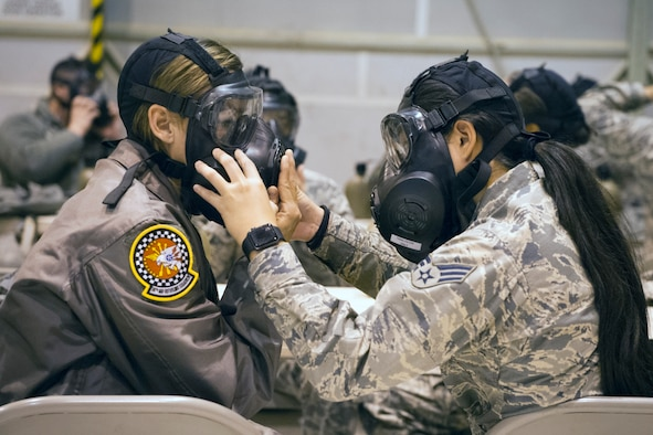 Airmen from the 434th Air Refueling Wing help check each other's mask seal during chemical, biological, radiological and nuclear defense training at Grissom Air Reserve Base, Indiana, Nov. 2, 2019. The training served as a refresher on how to survive and operate in lif-threatening chemical conditions. (U.S. Air Force photo/Staff Sgt. Courtney DotsonEssett.)