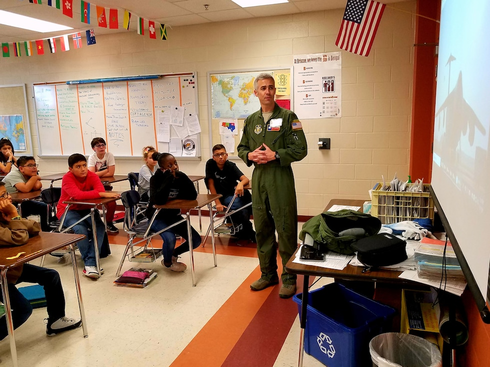 Maj. Matthew Menendez, 68th Airlift Squadron pilot, Joint Base San Antonio-Lackland, Texas briefs students from Dolph Briscoe Middle School, Nov. 11, 2019, on the mission of the 433rd Airlift Wing, and the facts about the aircraft they fly, the C-5M Super Galaxy.