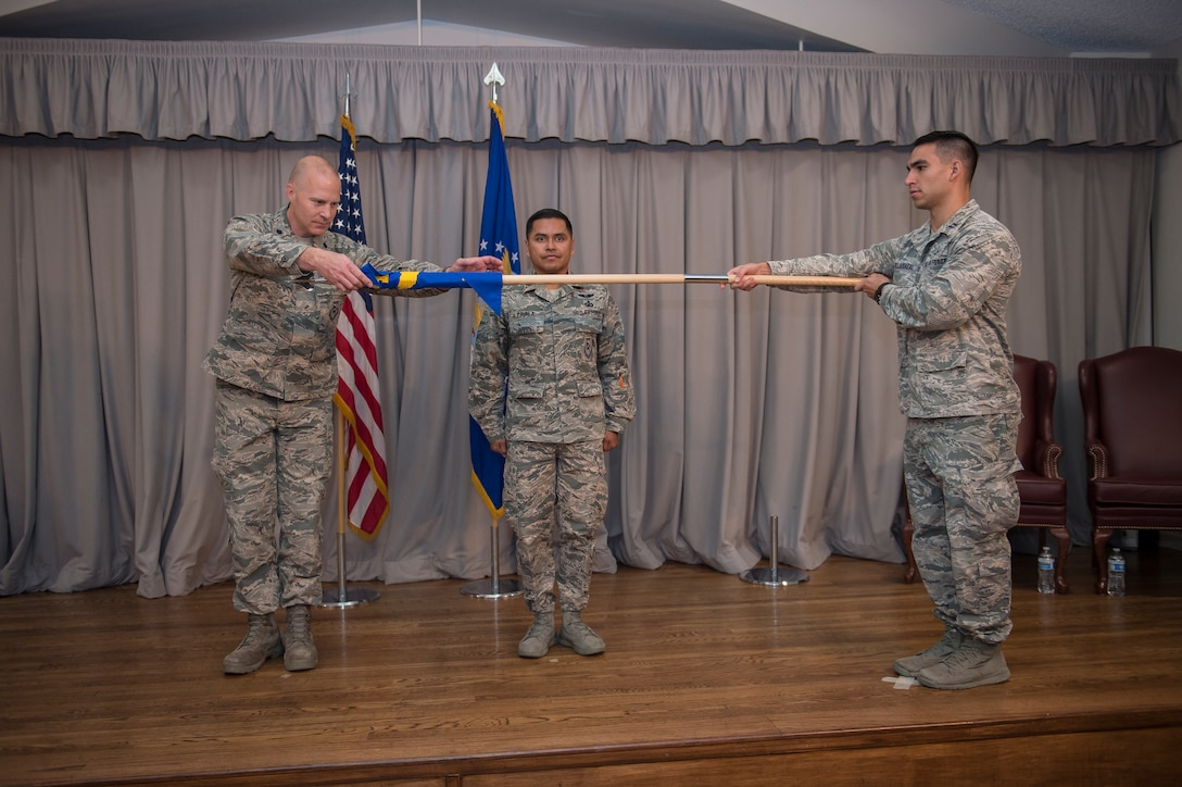 Lt. Col. Corey Beaverson, 47th Cyberspace Test Squadron Commander, unfurls the unit guidon for Detachment 1, 47th CTS, during the detachment's activation ceremony at Edwards Air Force Base, California, Nov. 19. Det. 1 will be commanded by Lt. Col. Ever Zavala (center). (Air Force photo by Joshua Miller)