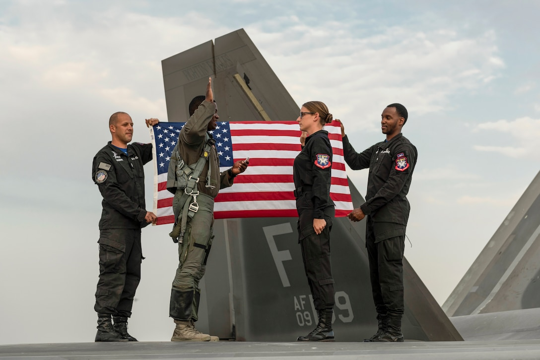 Two airmen face each other with right hands raised while standing atop a plane, as two others hold a U.S. flag behind them.