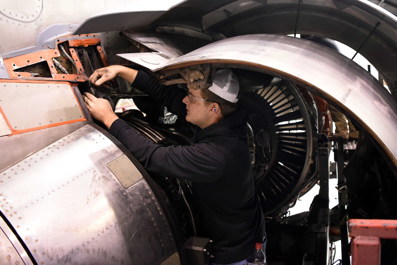 A man works on the engine of an aircraft.