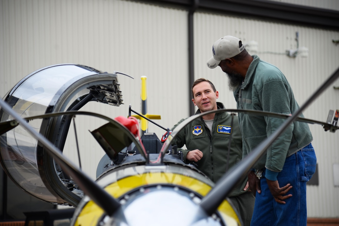First Lt. Cody Favorite, 37th Flying Training Squadron instructor pilot, shows a retiree guest the inner workings of a T-6 Texan II, Nov. 14, 2019, on Columbus Air Force Base, Miss. The day aligned with November's theme of military family appreciation and allowed Columbus AFB to show its gratitude for the retiree community. (U.S. Air Force photo by Airman 1st Class Jake Jacobsen)