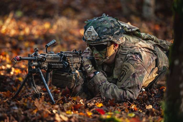 A soldier laying on the ground with a weapon scans an area.