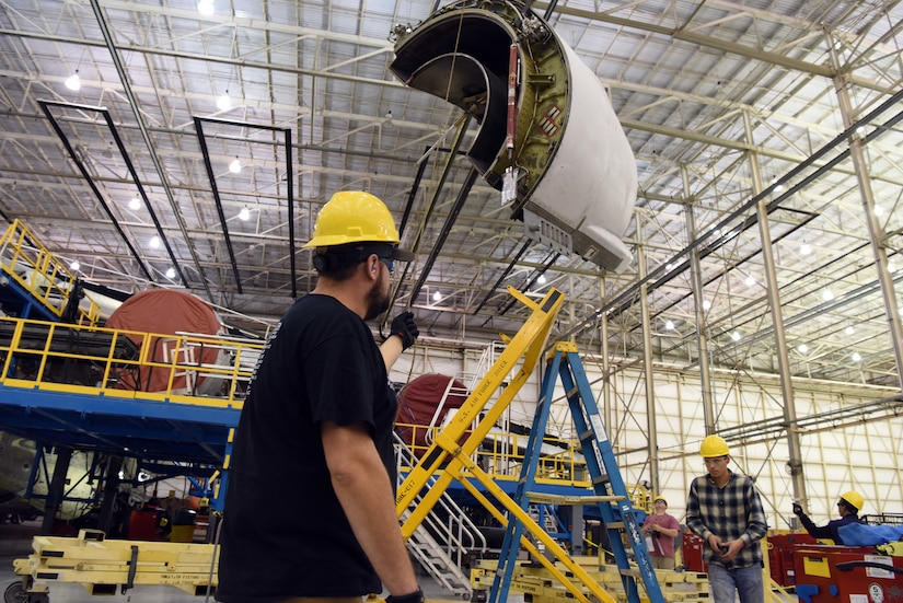 Men personnel work on aircraft in hangar.