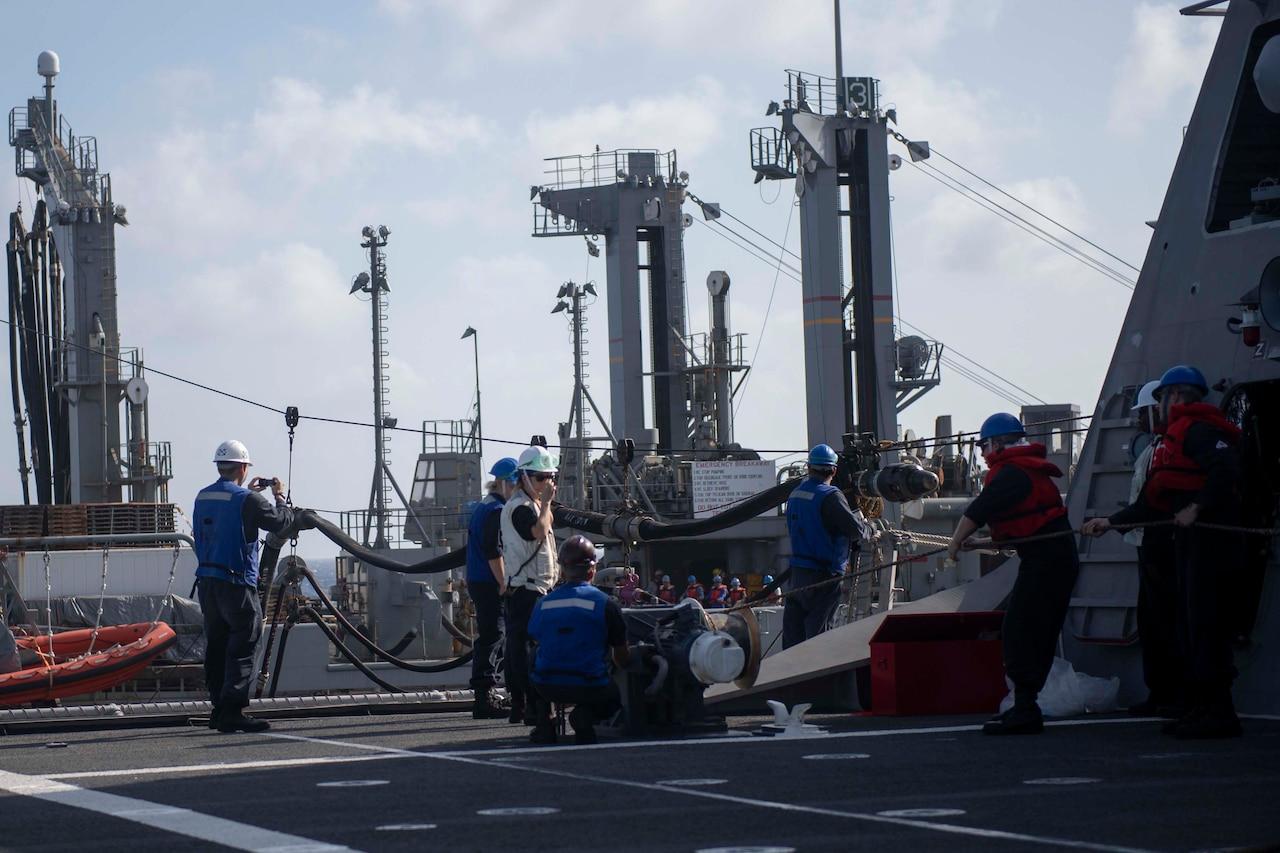 Sailors work on ship's deck.