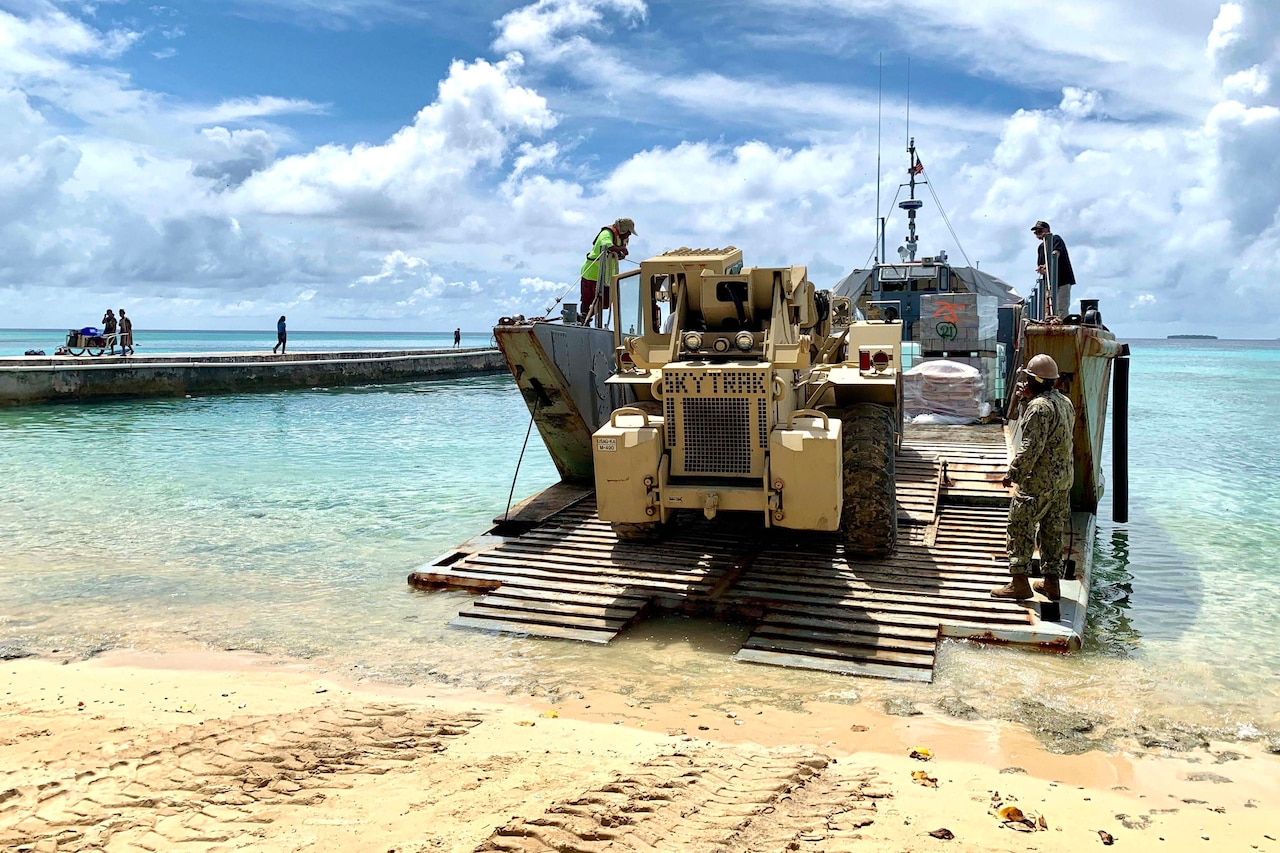 Personnel work on small boat on a beach.