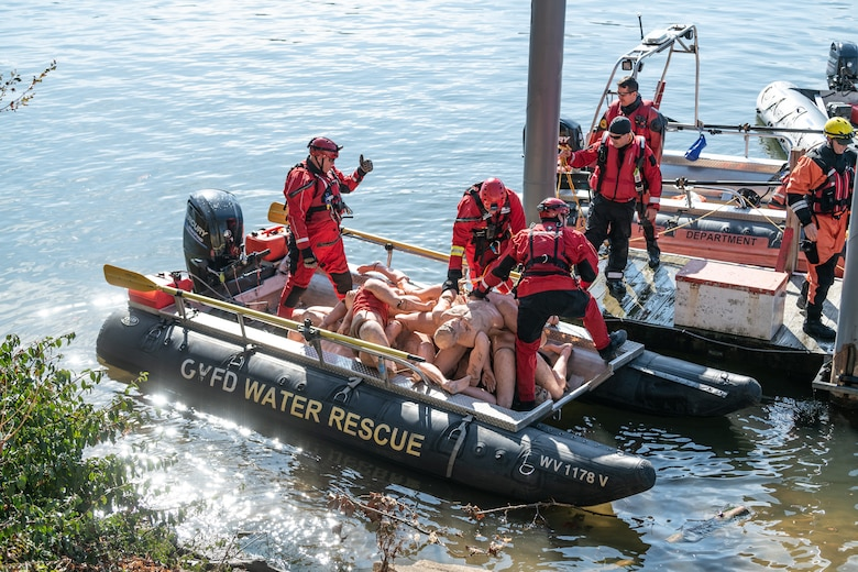 Swift water crew members in red wet suits and gear load mannequins into their boat prior to placement along the banks of the Kanawha River.