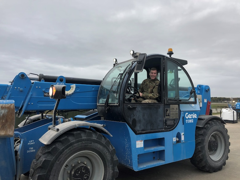U.S. Air Force Staff Sgt. Dylan Rymer, 435th Contingency Response Squadron aerial port journeyman, takes a break while operating a telehandler during Hybrid Airman training at Ramstein Air Base, Germany, Nov. 7, 2019. A telehandler unloads rapid-setting concrete sacks from a warehouse trailer and places them in a designated location for ease-of-use. (U.S. Air Force photo by Capt. Daniel McKeown)