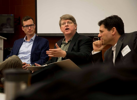 From left, August Cole, co-author of Ghost Fleet, Chuck Gannon, author of Trial by Fire, and Max Brooks, author of World War Z, talk with select group of burgeoning science fiction writers from across Department of Defense, February 4, 2019 (DOD/Kyle Olson)