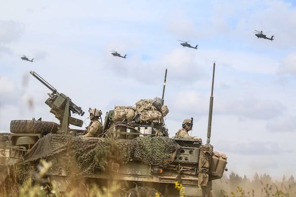 "Interim Armored Vehicle ""Stryker"" and AH-64 Apache helicopters with Battle Group Poland move to secure area during lethality demonstration at Bemowo Piskie Training Area, Poland, June 15, 2018, as part of Saber Strike 18 (U.S. Army/Hubert D. Delany)"