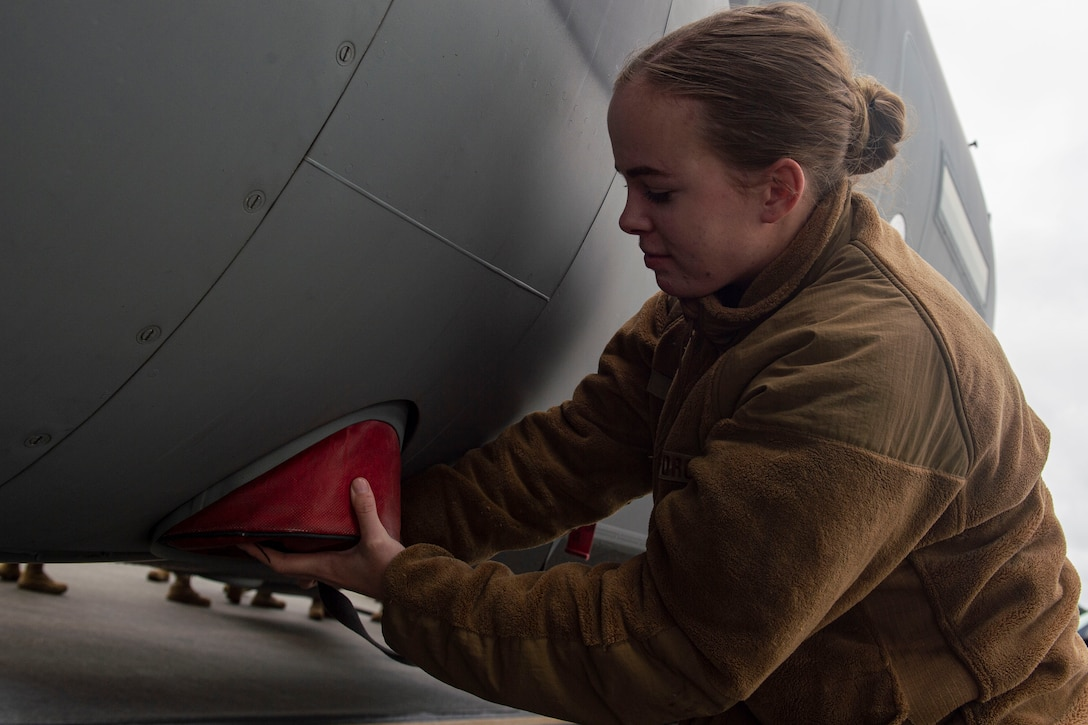 A photo of an Airman installing a plug onto the outside of an aircraft.