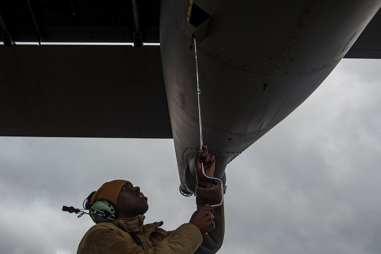 A photo of an Airman opening a compartment on an aircraft.