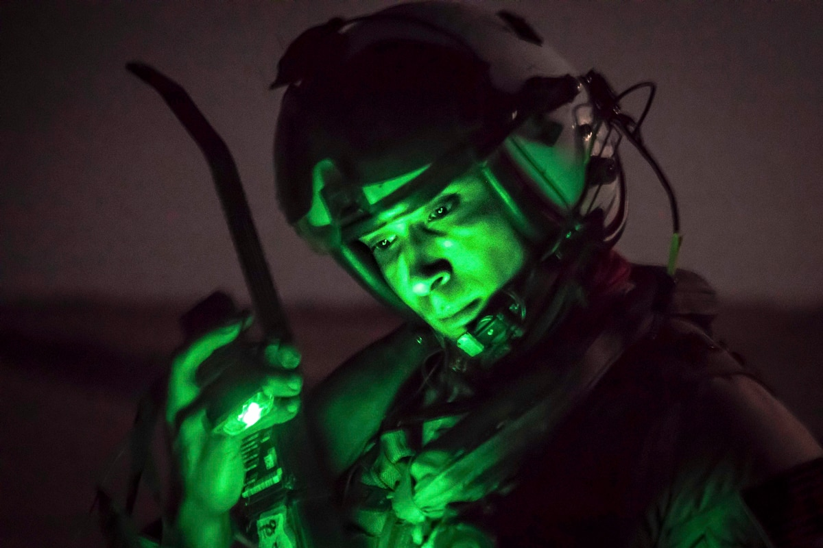 A sailor wears a helmet while illuminated by a green light.