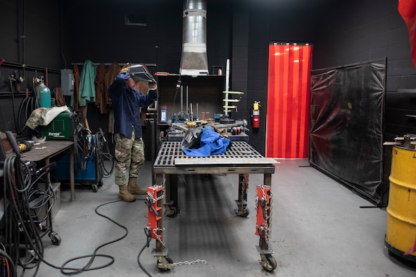 A photo of an Airman donning protective gear before welding a handrail
