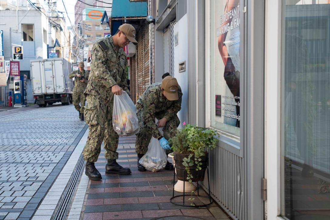 Two sailors hold trash bags on a city sidewalk.