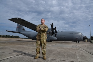 Tech. Sgt. Jonathan Parker, 815th Airlift Squadron instructor loadmaster, poses with an 815th AS, Flying Jennies, C-130J Super Hercules at Keesler Air Force Base, Miss. (U.S. Air Force photo by Jessica L. Kendziorek)