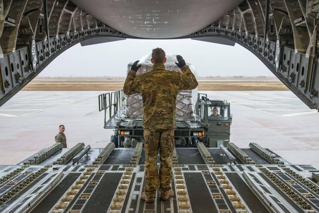 An airman stands inside an open aircraft and guides a vehicle carrying food.