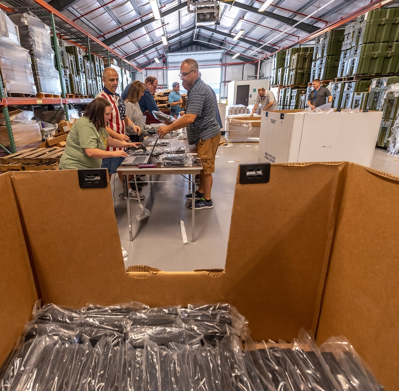 Photo of depot employees preparing thin client devices for distribution