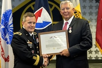 Brig. Gen. Mark S. Bennett, U.S. Army Financial Management Command commanding general, presents Joseph Myrda, USAFMCOM financial systems analyst, with an Army Superior Civilian Service Medal during Myrda's retirement ceremony in Indianapolis Nov. 21, 2019. Enlisting in the Army in 1963, Myrda served three tours in Vietnam, retired from the military as a command sergeant major in 1992, and served in a civil servant and a recognized expert in disbursing operations across the Army until his civilian retirement. (U.S. Army photo by Mark R. W. Orders-Woempner)