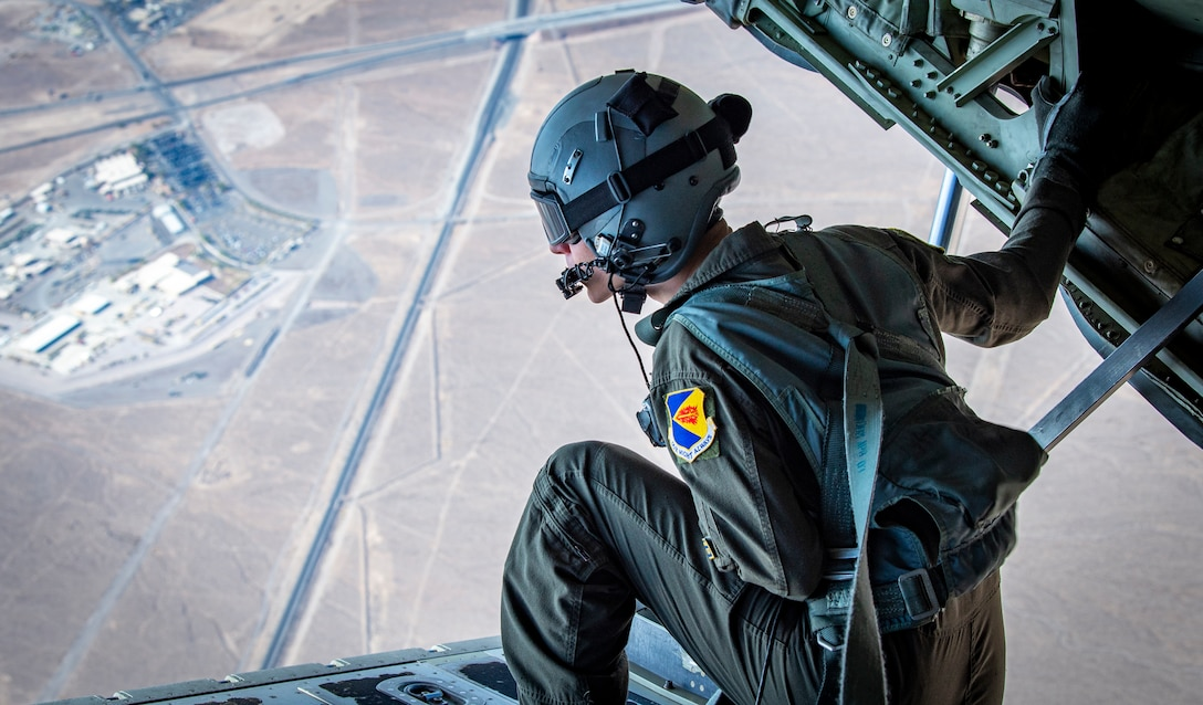 Airman 1st Class looks out of an HC-130J Combat King II