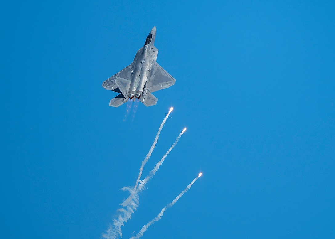 An F-22 Raptor fighter jet pops flares during air show