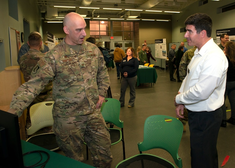U.S. Air Force Col. Michael Staples, 673d Civil Engineer Group commander, talks about noise contours with Jay Austin, an environmental analyst with Leidos, during an Air Installation Compatible Use Zone study open house in Anchorage, Alaska, Nov. 20, 2019. Joint Base Elmendorf-Richardson, Alaska, hosted the event, which showed the results of the study, to promote transparency between the installation and its community partners.