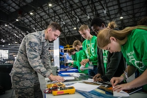 Staff Sgt. Robert Gentry, 932nd Airlift Wing Maintenance Squadron technician, speaks with students about maintenance careers within the Air Force Reserve and challenges students to create and fly paper airplanes during STEAM Day at Scott Air Force Base, Illinois, Nov. 20, 2019. The day inspires kids to explore and pursue their interests in Science, Technology, Engineering, Art and Math.  (U.S. Air Force photo by Christopher Parr)