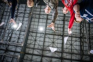Staff Sgt. Robert Gentry, 932nd Airlift Wing Maintenance Squadron technician, joins STEAM Day local school students as they compete for the longest flight with a paper airplane during during the STEAM Day event at Scott Air Force Base, Illinois, Nov. 20, 2019. The day inspires kids to explore and pursue their interests in Science, Technology, Engineering, Art and Math.