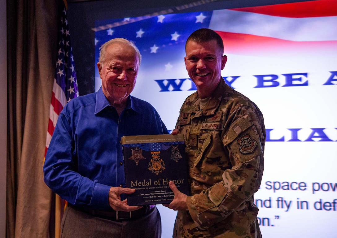 Retired U.S. Army Col. Bruce Crandall, a Medal of Honor recipient, right, presents the book Medal of Honor to U.S. Air Force Col. Scovill Currin, 62nd Airlift Wing commander, left, at Joint Base Lewis-McChord (JBLM), Wash., Nov. 21, 2019. Crandall visited JBLM to talk about his time in the Army during a professional development presentation. (U.S. Air Force photo by Senior Airman Tryphena Mayhugh)