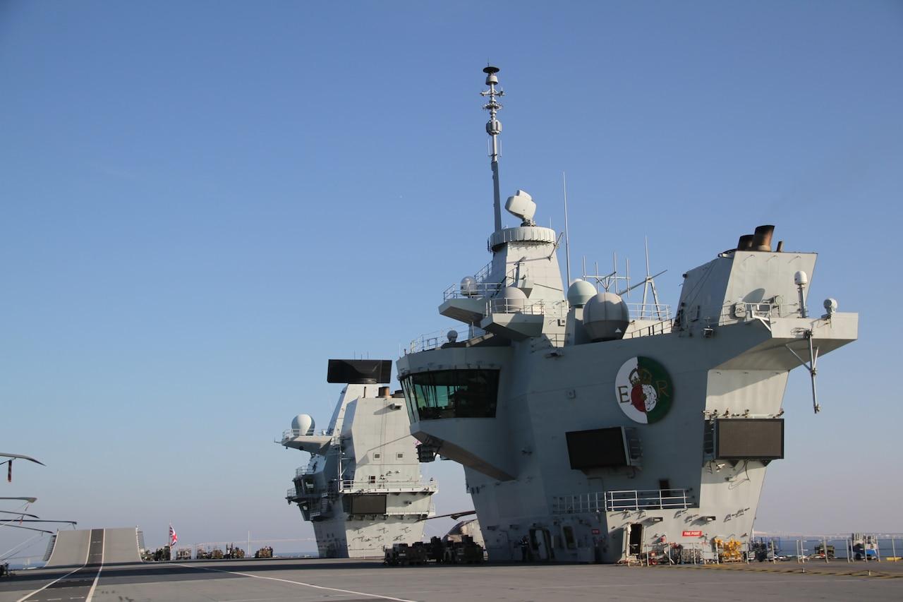 """Two """"islands"""" tower over an aircraft carrier's flight deck."""