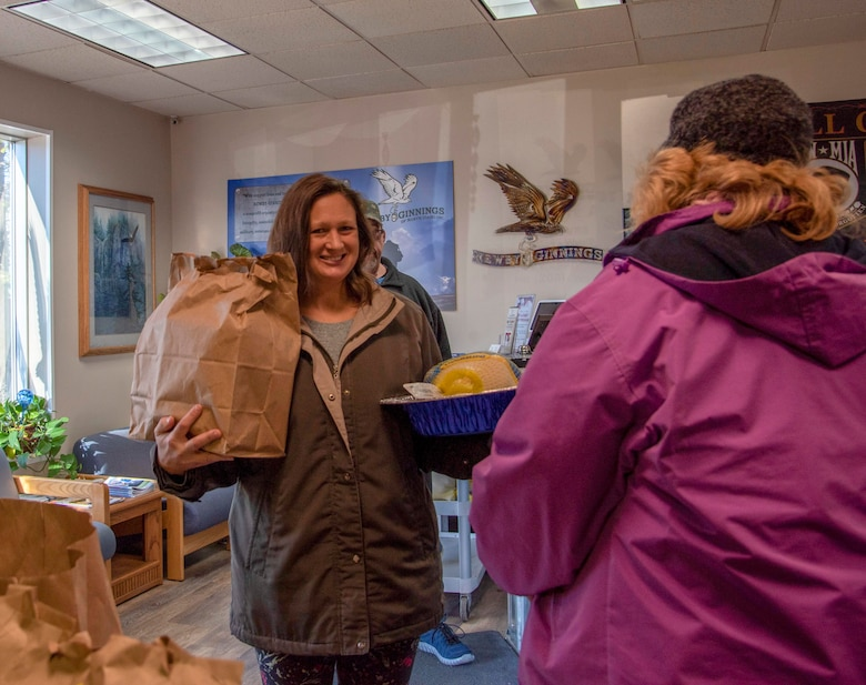 A member of the local community receives a Thanksgiving meal bag and turkey at Newby-ginnings in Post Falls, Idaho, Nov. 14, 2019.