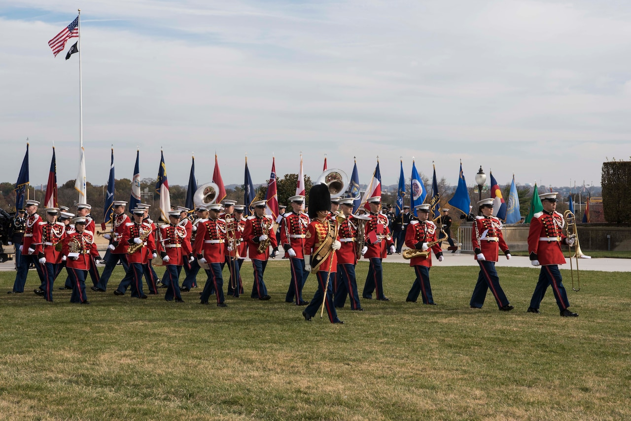 Military band members wearing red jackets and blue trousers and carrying their instruments march in salute.