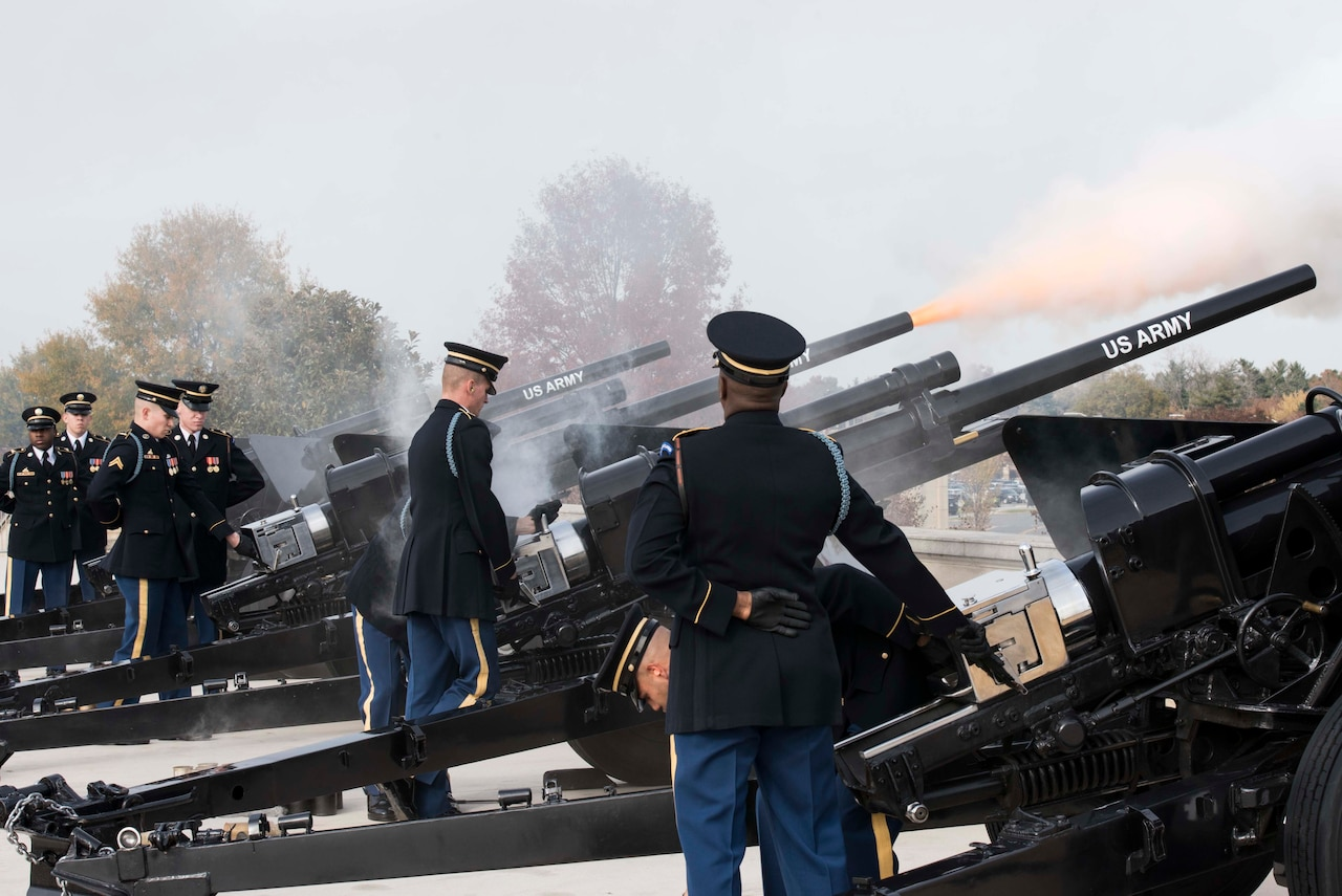 Service members fire canons.