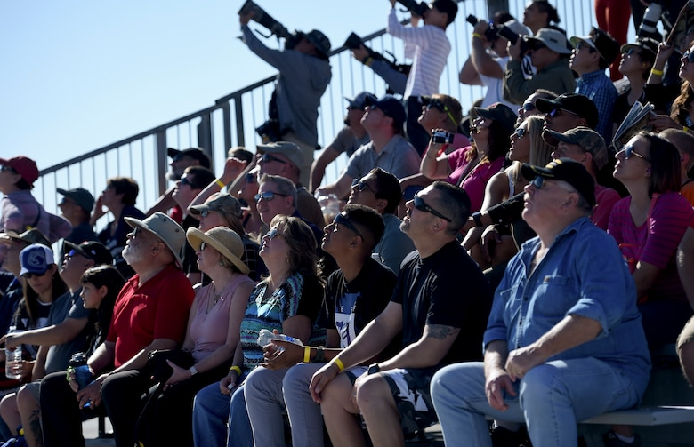 Aviation Nation attendees look to the sky as the MQ-9 Reaper flies by, at Nellis Air Force Base, Nevada, Nov. 16, 2019. Even though the MQ-9 Reaper static display is normally available at Nellis' Aviation Nation, this is the first time an MQ-9 has performed a flyover. (U.S. Air Force photo by Airman 1st Class William Rio Rosado)