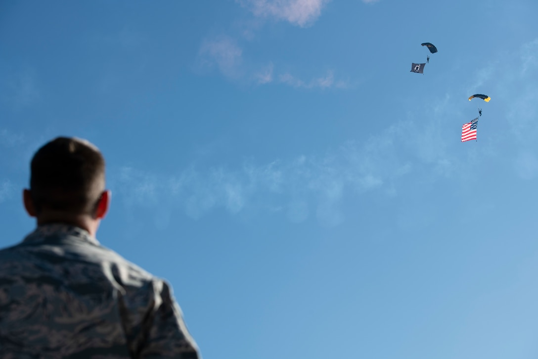 A Creech Airman watches Special Operations Command Para-Commandos parachute during the opening ceremony of Aviation Nation, at Nellis Air Force Base, Nevada, Nov. 16, 2019. The SOCOM Para-Commandos performed a parachute demonstration during the opening ceremonies of Aviation Nation. (U.S. Air Force photo by Staff Sgt. Omari Bernard)