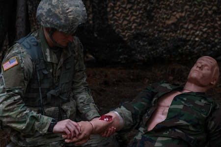 U.S. Army Staff Sgt. Edward Chase, a drill sergeant with the 2-39 Infantry Battalion, 165th Inf. Brigade at Fort Jackson, examines a wound during the medical lane of the Expert Soldier Badge course at Joint Base Langley-Eustis, Virginia, Nov. 18, 2019. There were 10 tasks in the medical lane, including requesting medical evacuation, providing care under fire, moving a casualty and controlling blood loss.  (U.S. Air Force photo by Senior Airman Derek Seifert)