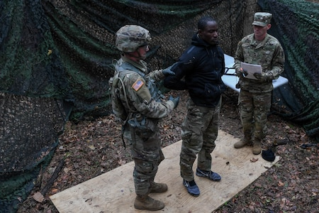 U.S. Army Spc. Keenan Baker, a military policeman with the 108th Military Police at Fort Bragg, searches a suspect during a task in the weapons lane during the Expert Soldier Badge course at Joint Base Langley-Eustis, Virginia, Nov. 18, 2019. To be awarded the ESB, Soldiers must pass 30 tasks designed to enhance the lethality and readiness of the force. (U.S. Air Force photo by Senior Airman Derek Seifert)