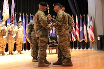 Col. Stallings passes the sword of the noncommissioned officer to Command Sgt. Maj. Russell, incoming command sergeant major, signifying the change of responsibility between Russell and Command Sgt. Maj. Multunas during the Recruiting and Retention College Change of Responsibility that took place at Fort Knox, Kentucky Nov. 21.