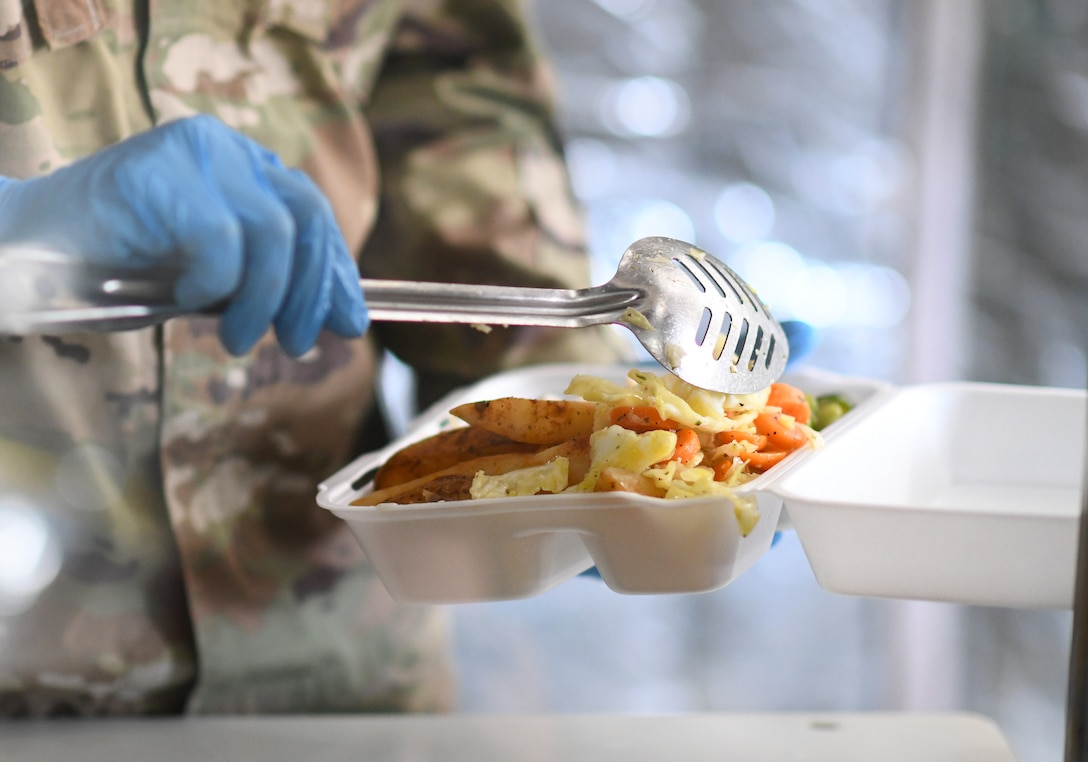 A member of the 776th Expeditionary Air Base Squadron Services team serves food to dining facility patrons at Chabelley Airfield, Djibouti, Nov. 13, 2109. The services Airmen receive, inspect, prepare and serve roughly 800 meals each day to Airmen, Soldiers and contractors fulfilling their duties on the airfield. (U.S. Air Force photo by Staff Sgt. Alex Fox Echols III)