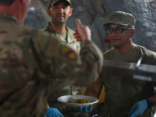 U.S. Air Force Staff Sgt. Carlos Ortega, left, and Tech. Sgt. Juan Serrano, 776th Expeditionary Air Base Squadron Services food and beverage NCO in-charge and assistant manager, serve food to dining facility patrons at Chabelley Airfield, Djibouti, Nov. 13, 2109. Like most of the 776th EABS services team, Ortega and Serrano are deployed from the 156th Wing, Puerto Rico Air National Guard at Muñiz Air National Guard Base, Carolina, Puerto Rico. (U.S. Air Force photo by Staff Sgt. Alex Fox Echols III)