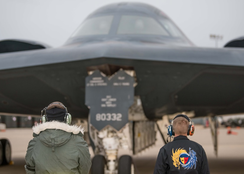 A view of the back of two crew chiefs who are looking at B-2 Spirit Stealth Bomber in front of them.