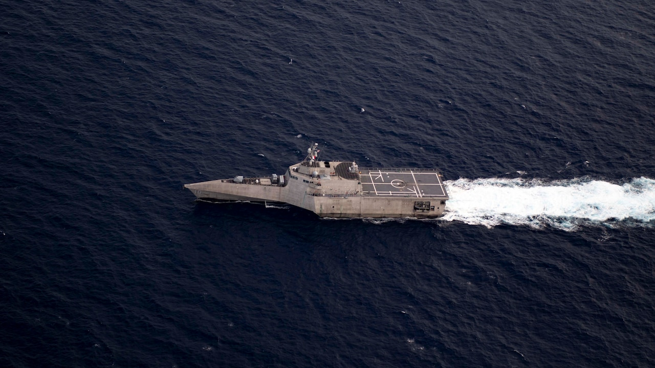 A littoral combat ship sails in the sea leaving a white wake behind.