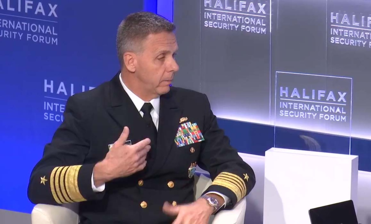A navy admiral in uniform speaks from a white arm chair.
