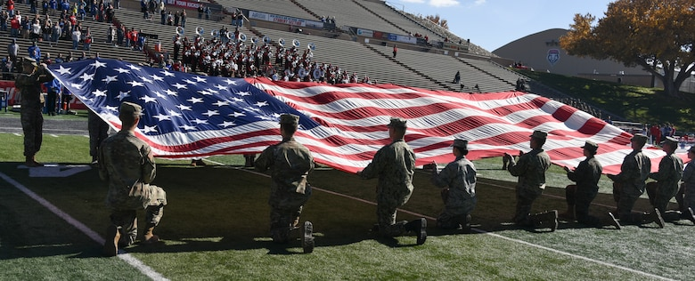 Photo of ROTC cadets holding large american flag