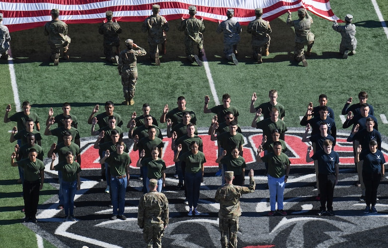 Photo of future service members getting sworn in on football field.