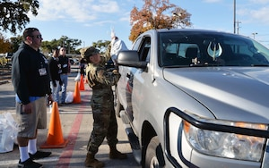 Maj. Jaime Barker, 433rd Civil Engineer Squadron commander, JBSA-Lackland Texas hands a turkey to a military family at the ninth annual Turkeys for Troops event at Toyota of Boerne Nov. 22, 2019 in Boerne, Texas. Nearly 8000 turkeys were given away to military members, veterans, and military families. (U.S. Air Force photo by Master Sgt. Kristian Carter)