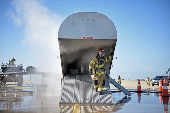 A U.S. Air Force firefighter assigned to the 8th Civil Engineer Squadron exits an aircraft fire trainer during a live fire simulation at Kunsan Air Base, Republic of Korea, Nov. 20, 2019. Live fire training ensures active duty firefighters are prepared for emergencies on the installation while also maintaining readiness. (U.S. Air Force photo by Staff Sgt. Mackenzie Mendez)